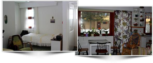 Rantapellontien asunnosta vasemmalla makuusyvennys, jossa valkoiset seinät, ikkuna, pedattu vuode, vihreä keinutuoli, seinillä tauluja. Oikealla ruokailutila, jossa pieni pöytä ikkunan ääressä, kolme tuolia, ikkunalaudalla monta viherkasvia, värikkäät verhot ja seinähyllyt joilla esineitä.