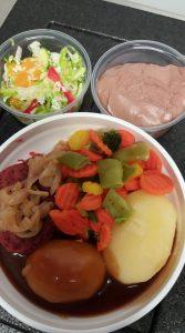Värikäs lounasruoka-annos, jossa pienemmissä kupeissa värikäs salaatti, marjarahka ja lautasella perunaa, kastiketta, lihaa ja kasviksia.