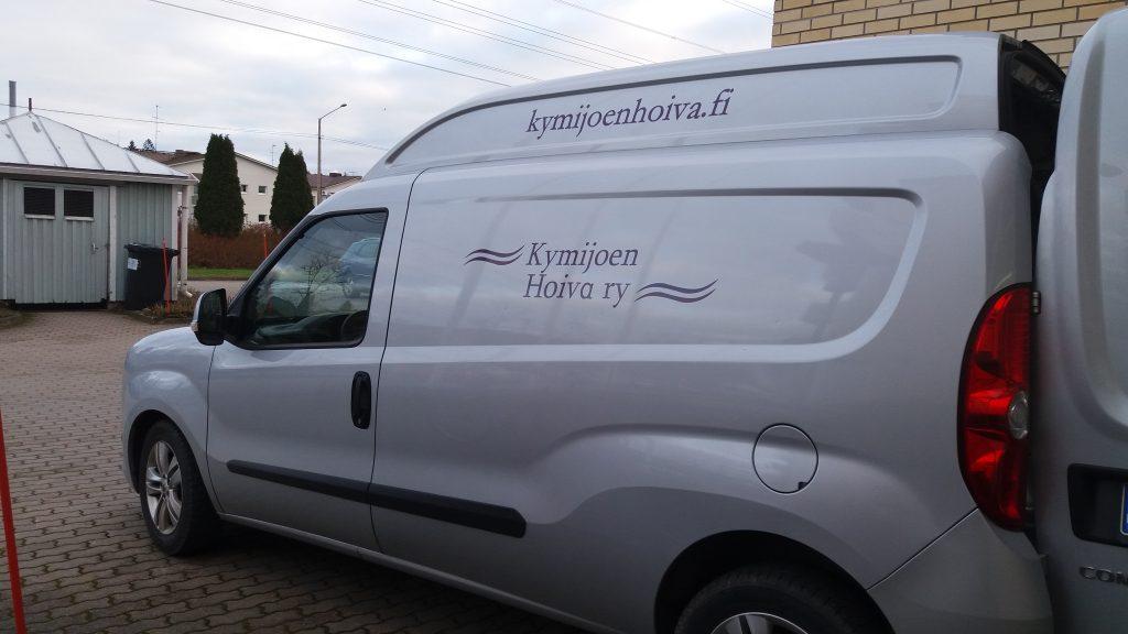 Kymijoen Hoivan vaaleanharmaa pakettiauto, kyljessä Kymijoen hoivan logo.