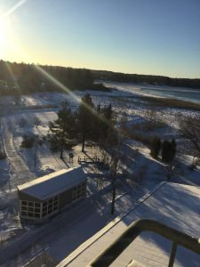 Näkymä parvekkeelta lumiselle takapihalle ja Kymijoelle auringon paistaessa kirkkaasti.