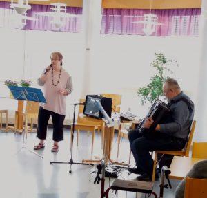 Marja-Terttu Riihelä laulaa ja Markku Seppälä säestää haitarilla ravintola Syreenin ruokasalissa.