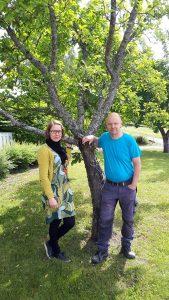 Tuuli ja Esa seisovat vihreällä takapihalla omenapuun edessä.