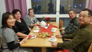 Japanilaisia vieraita talon henkilökunnan kanssa kahvipöydässä.