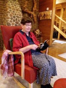 Eeva Ukkola istuu punaisessa keinutuolissa neulomassa, kodikkassa ympäristössä.