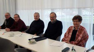 Yhdistyksen hallituksen jäsenet hymyilevinä ruokapöydän ääressä, edessään kahvikupit ja kokouspapereita.
