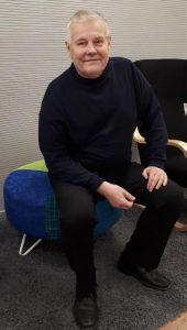Matti Heino istuu hymyilevänä.