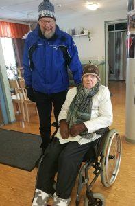 Pekka Reponen sinisessä toppatakissa ulkoiluttamassa pyörätuolissa istuvaa rouvaa.