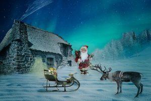 Joulukortti, jossa sininen hämyinen, luminen maisema, kivinen talo ja pihalla joulupukki, reki ja poro.