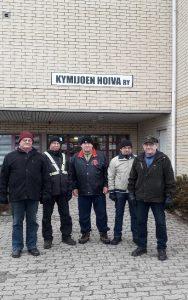Hutikoiden miehiä seisoo Kymijoen Hoivan senioritalojen sisäänkäynnin luona ulkoiluvaatteissa.