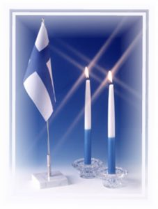 Suomen lippu ja kaksi sinivalkoista kynttilää palamassa.