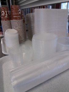 Läpinäkyviä pakkausrasioita sekä ruskeita kertakäyttöisiä kahvimukeja pinoissa.
