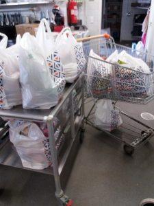 Täysinäisiä muovisia ostoskasseja ostoskärryissä.