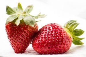 kaksi hehkuvanpunaista mansikkaa.