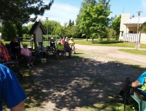 Ihmisiä pelaamassa mölkkyä Kymijoen Hoivan takapihalla auringonpaisteessa.