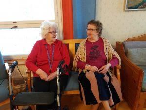 Kaksi ikääntyvää rouvaa istuu sohvalla ja juttelee hymyillen.