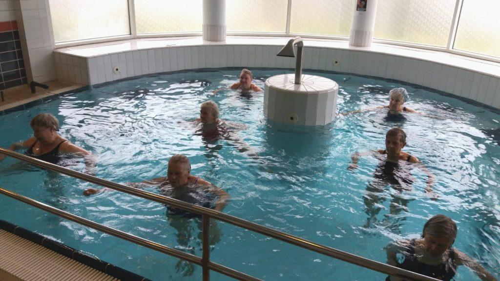 Kymijoen Hoivan uima-altaalla vedessä seitsemän vesivoimisteluryhmän naista uimapuvut päällä voimistelemassa.