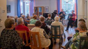 Paljon ikääntyviä ihmisiä istumassa ja katsomassa lauluesitystä hyvinvointiasemalla.