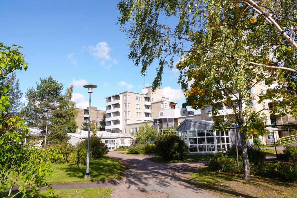 Kymijoen Hoivan senioritalot takapihalta päin, kirkkaassa auringonpaisteessa keltaiset kerrostalot sekä vihreä takapiha, jossa paljon puita.
