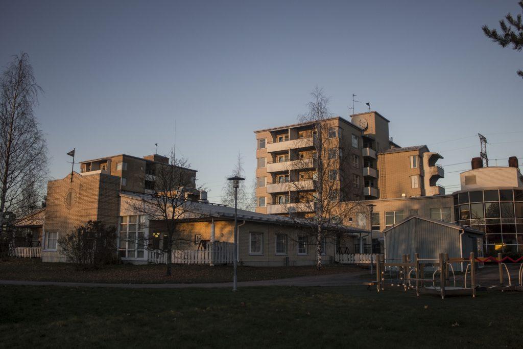 Kymijoen Hoivan Inkeroisten rakennukset takapihalta päin, ilta-auringossa keltaiset kerrostalot sekä vihreää takapihaa.