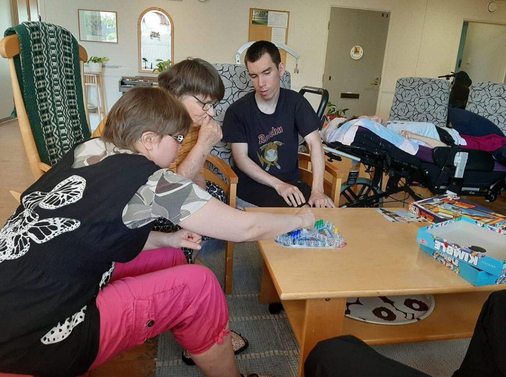 Kaksi naista ja yksi mies pelaavat Kimbleä ryhmäkodin oleskelutiloissa pöydän ääressä nojatuoleissa istuen.