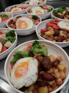 Kotiinkuljetusastioihin pakattuja aamupala-annoksia, joissa on pyttipannua, paistettua kananmunaa ja värikkäitä kasviksia.