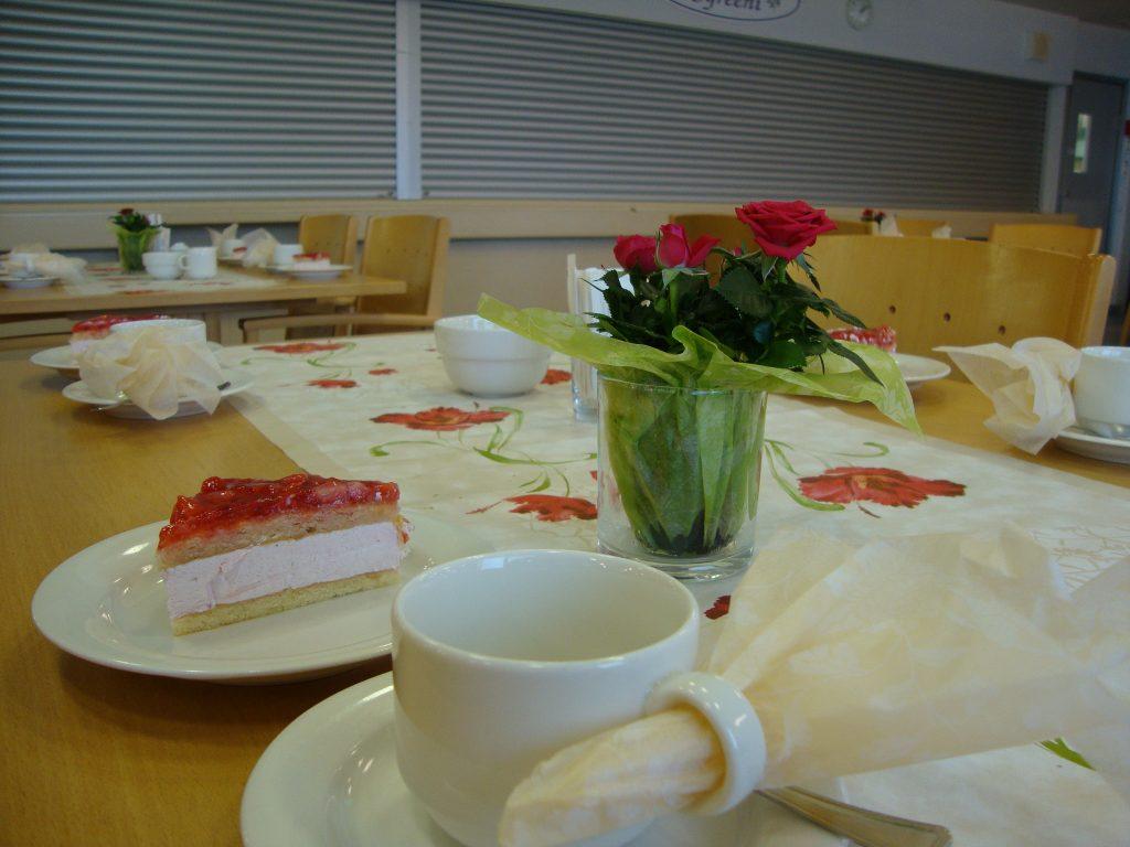 Ravintola Syreenissä juhlapöydät katettuna, pöydissä kukkakuvioiset liinat, ruusuja maljakossa, kahvikupit servetteineen, mansikka-kermakakkua lautasilla tarjolla.