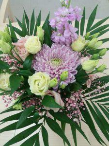 Pöydällä on kaunis kukkakimppu, jossa on valkoisia ja sinisiä kukkasia.