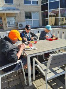 Kolme ihmistä istuu ulkona terassilla pöydän ääressä syömässä lounasruokaa.