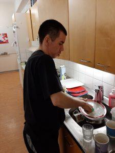 Ihminen tiskaamassa astioita.