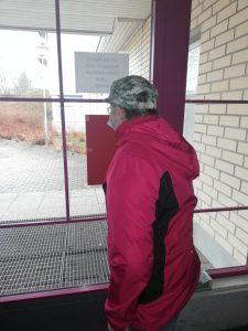 Asukas seisoo ulko-ovella ja odottaa taksin tulemista ja päivätoimintaan lähtöä.